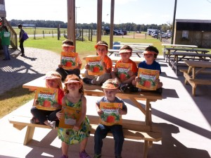 """VPK Children from Roots & Wings Preschool in St. Augustine, show off their new fall visors while they hold their free """"Spookley"""" book they received."""