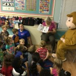 ELC reading volunteer Sara Pines and special guest Curious George read books from the book bag project to children at Green Gables Learning Center in Palatka.