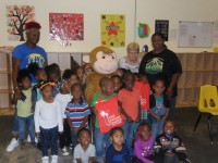 Curious George and ELC of North Florida volunteers deliver book bags to children at God's Little Creations Learning Center in Palatka.