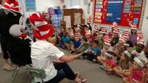 "ELC volunteers Ginny Dozier and Erika Bauserman with special guest the Cat in the Hat reading the book ""Ten Apples Up on Top"" by Dr. Seuss to children at Brighton Day Academy in St. Augustine"
